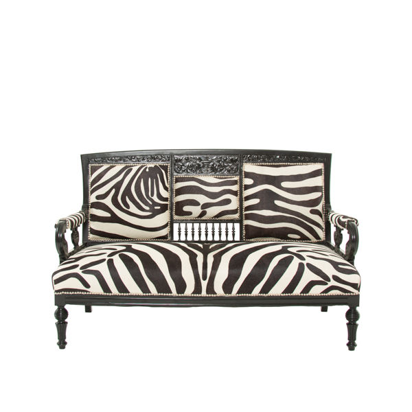 zebra hide upholstered sette with silver nailheads and black wooden trim