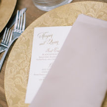 Gold embossed floral charger with menu and blush napkin.